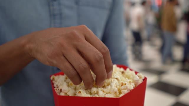 stockvideo's en b-roll-footage met onherkenbaar man op de films eten pop maïs - popcorn