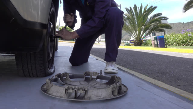 unrecognizable man changing a flat tire - lug wrench stock videos and b-roll footage