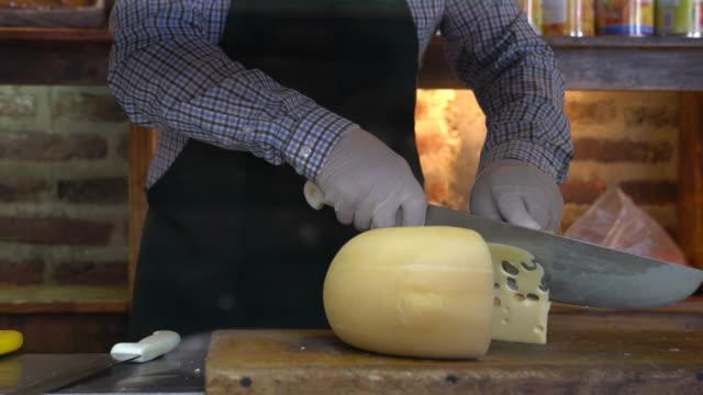 vidéos et rushes de fromage méconnaissable de coupe d'homme à une épicerie fine - culture française