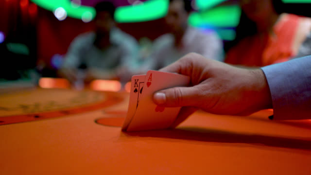 vídeos de stock e filmes b-roll de unrecognizable man gambling at the poker table lifting his cards to look at them - carta de baralho