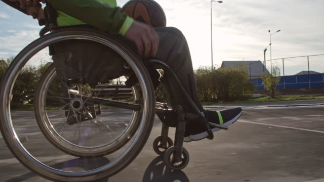 unrecognizable man in wheelchair dribbling ball in slow - wheelchair stock videos and b-roll footage