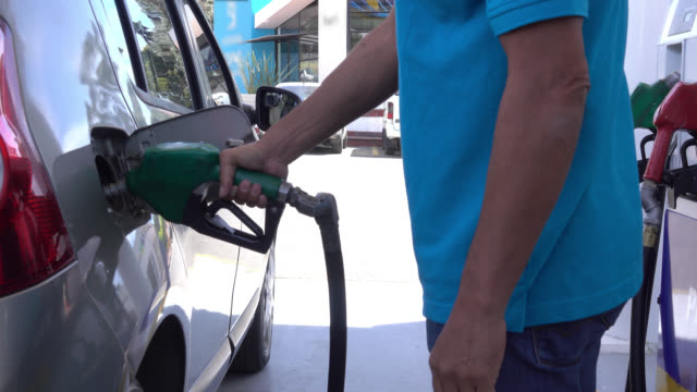 unrecognizable man refueling his car at a gas station - refuelling stock videos & royalty-free footage