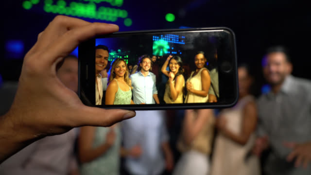 unrecognizable man taking a photo of a group of people having fun at a bar dancing - disco dancing stock videos & royalty-free footage