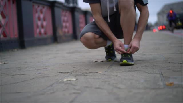 vidéos et rushes de méconnaissable homme attachant sa chaussure de tennis pour commencer à courir - nouer