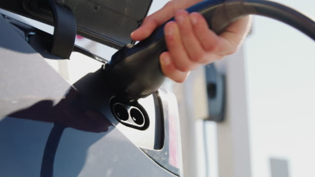 slo mo unrecognizable man unplugging an ev plug from a vehicle inlet - absence stock videos & royalty-free footage
