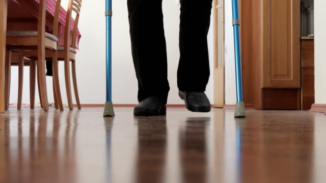 unrecognizable man walking with crutches in domestic room - wooden floor stock videos & royalty-free footage