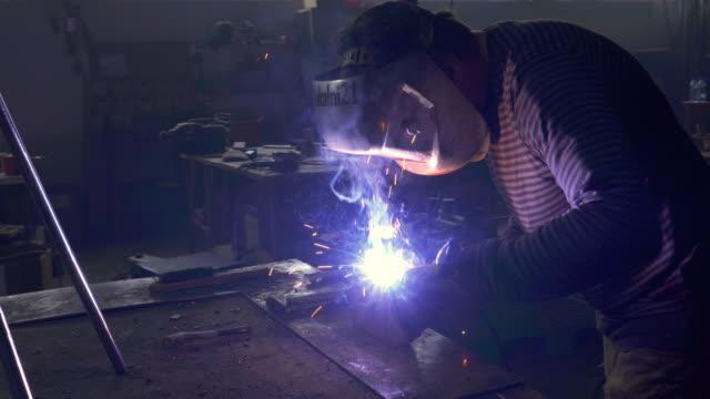 Oigenkännlig arbetare svetsning järn i en workshop.