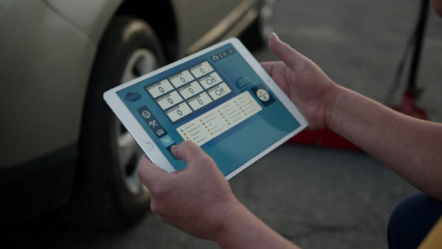 unrecognizable mechanic using tablet to check pressure of vehicle wheels - examining stock videos & royalty-free footage