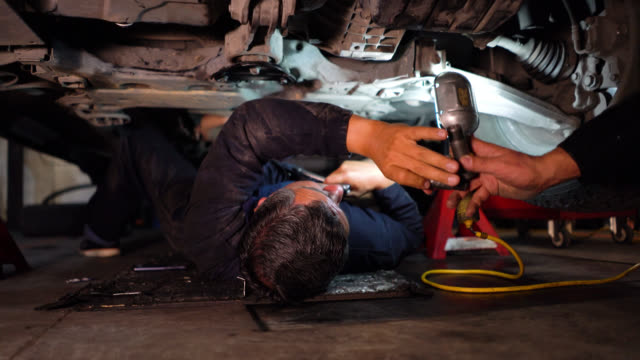 Unrecognizable mechanic working under a car using a tool