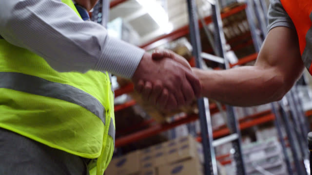 unrecognizable men closing a deal at a warehouse distribution handshaking - world trade organisation stock videos & royalty-free footage