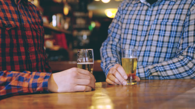 DS CU Unrecognizable men toasting with beer in the pub