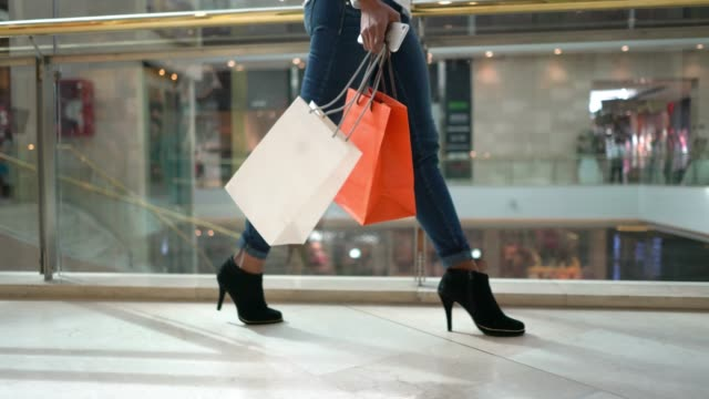 unrecognizable modern woman walking around the mall holding her shopping bags and smartphone - shopping centre stock videos & royalty-free footage