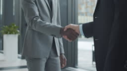 Unrecognizable Multiethnic Businessmen Shaking Hands in Office Hallway