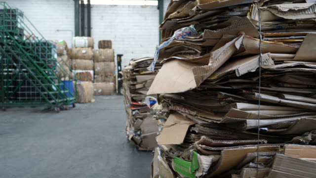 unrecognizable operator of a forklift truck stacking bulks of cardboard boxes at a recycling center - stack stock videos & royalty-free footage