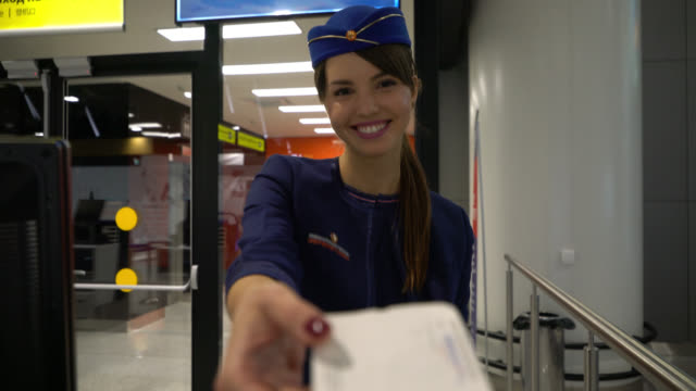 unrecognizable passenger handing boarding pass to friendly flight attendant before boarding the plane - sala d'imbarco video stock e b–roll