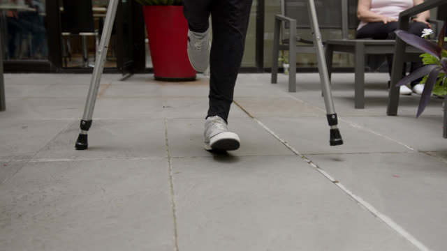 unrecognizable patient leaving after physical therapy crossing a patio - crutch stock videos & royalty-free footage