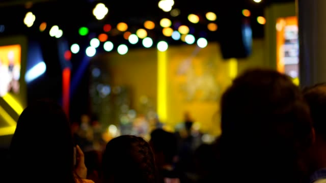 unrecognizable people at a concert crowed of people cheering in front of bright and blured colorful stage lights. - dj stock videos & royalty-free footage