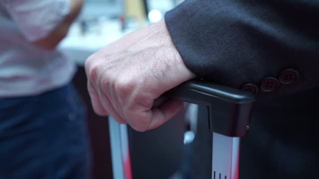 persone irriconoscibili trascinano i bagagli in aeroporto - imbarcarsi video stock e b–roll
