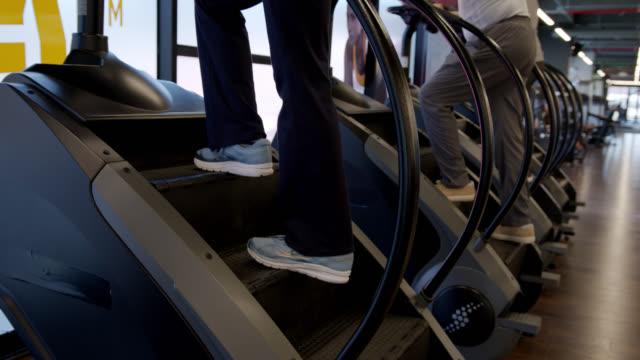 vidéos et rushes de personnes méconnaissables sur des machines de stepper à la gymnastique - entraînement cardiovasculaire