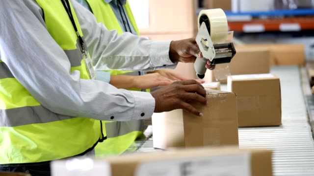 Unrecognizable people seal packages in distribution warehouse