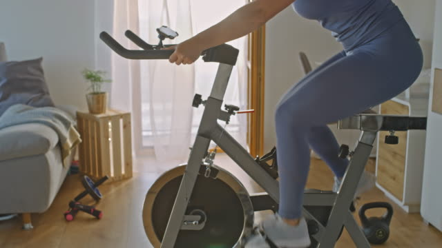 slo mo unrecognizable person exercising on the exercise bike - exercise bike stock videos & royalty-free footage