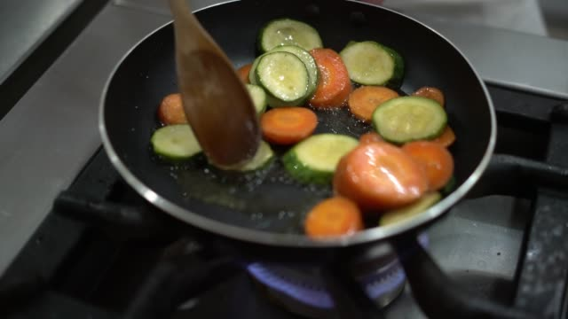 Unrecognizable person frying carrots and zucchinis