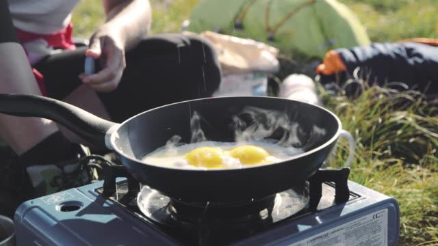 キャンプストーブで卵を揚げるds認識できない人 - キャンプ用ストーブ点の映像素材/bロール