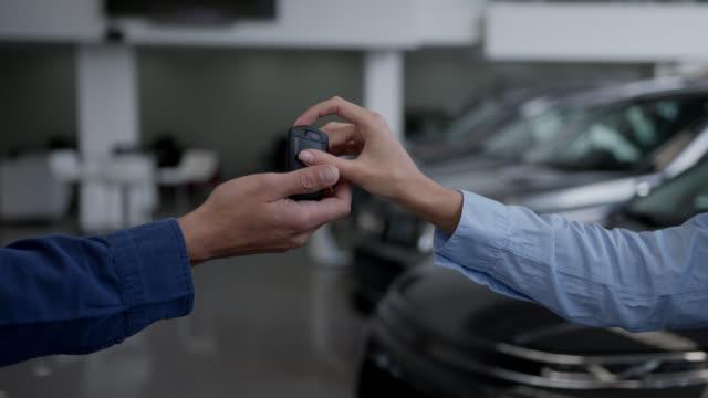 vídeos y material grabado en eventos de stock de persona irreconocible entregando las llaves al cliente en un concesionario de automóviles - dar