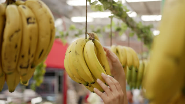 unrecognizable person hanging bananas at a farmer's market stall - hanging stock videos & royalty-free footage