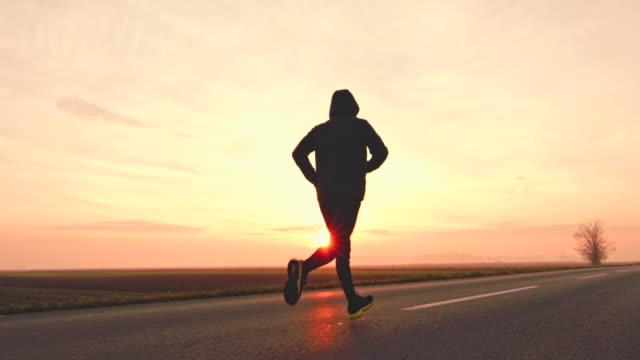 slo mo unrecognizable person in hooded sweatshirt jogging at sunset - cappuccio video stock e b–roll