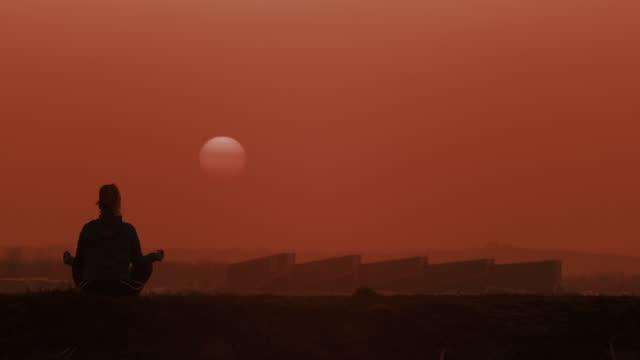 stockvideo's en b-roll-footage met slo mo ls onherkenbare persoon in silhouet dat op een heuvel bij zonsondergang mediteert - lotuspositie