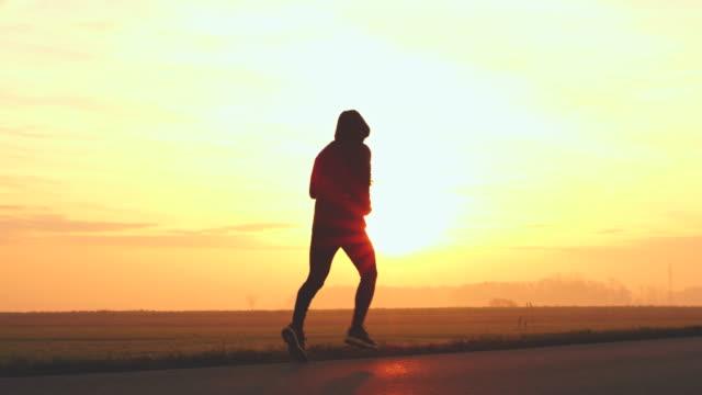 WS oigenkännlig person jogging på en landsväg