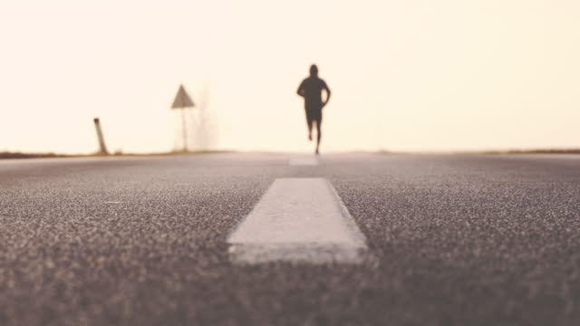 slo mo unrecognizable person jogging on the road to nowhere - focus on foreground stock videos & royalty-free footage