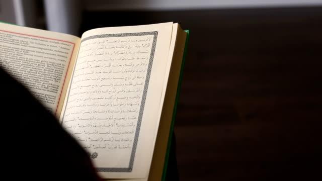 dolly shot: unrecognizable person reading holy koran - koran stock videos & royalty-free footage