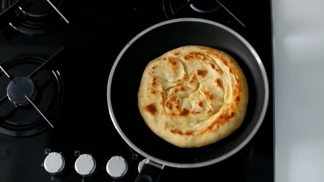 Unrecognizable person shaking the frying pan while cooking delicious pita or flatbread in the kitchen