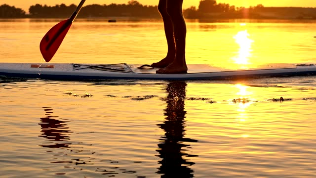 slo mo unrecognizable person stand-up paddleboarding - using a paddle stock videos & royalty-free footage