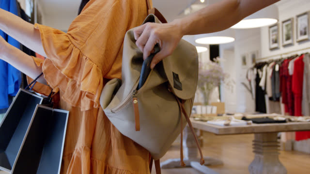 unrecognizable person stealing a smartphone from a customers bag at a clothing boutique - thief stock videos & royalty-free footage