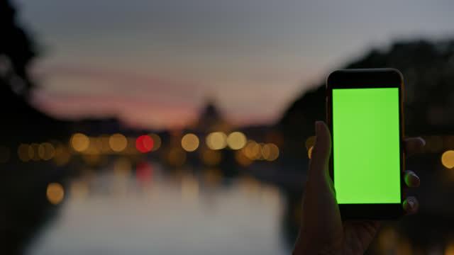 夕暮れ時にサンタンジェロポンを撮影するためのクロマキーディスプレイ付きのスマートフォンを使用してslo mo認識できない人 - サンタンジェロ橋点の映像素材/bロール