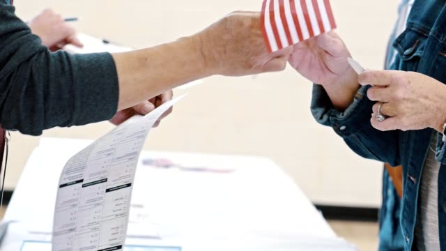 vídeos de stock e filmes b-roll de unrecognizable polling place volunteer gives small american flag to a voter - eleições