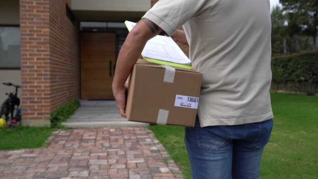 unrecognizable postal worker delivering a package at a house looking at a clipboard with document - postal worker stock videos & royalty-free footage