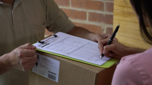 unrecognizable postal worker delivering box to woman at home while she signs a sheet - post office stock videos & royalty-free footage