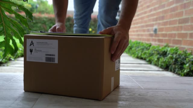 unrecognizable postal worker leaving a box on front porch of home - porch stock videos & royalty-free footage