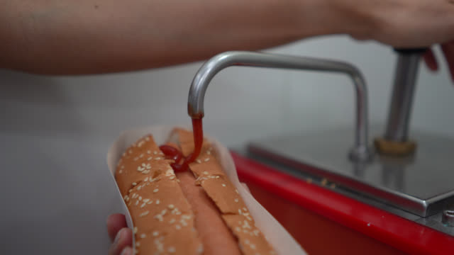 unrecognizable saleswoman adding ketchup to hotdog at the cinema concession stand - ketchup stock videos and b-roll footage