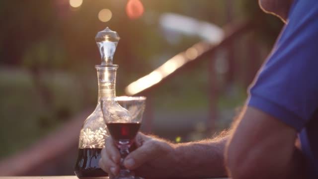 vidéos et rushes de homme aîné méconnaissable appréciant un verre de vin pendant un coucher du soleil - un seul homme