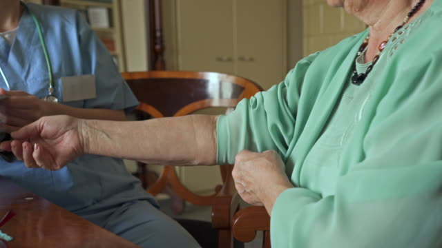 unrecognizable senior woman getting her blood pressure measured by female healthcare worker. - sheltered housing stock videos & royalty-free footage