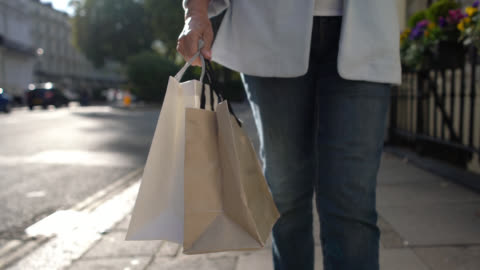 unrecognizable senior woman on a shopping spree holding bags and walking down the street - paper bag stock videos & royalty-free footage
