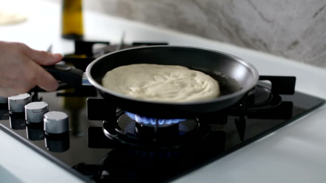 DOLLY: Unrecognizable senior woman shaking the frying pan while cooking delicious pita or flatbread in the kitchen
