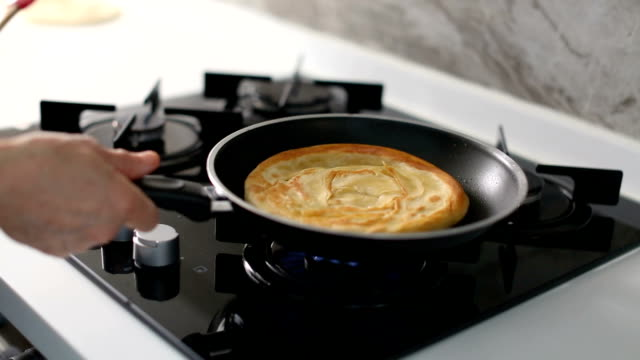Unrecognizable senior woman shaking the frying pan while cooking delicious pita or flatbread in the kitchen
