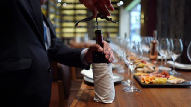 認識できないソムリエは、ワインの試飲の準備ができて、提供されたテーブルの上にコルクねじでワインボトルを開きます - ワインバー点の映像素材/bロール