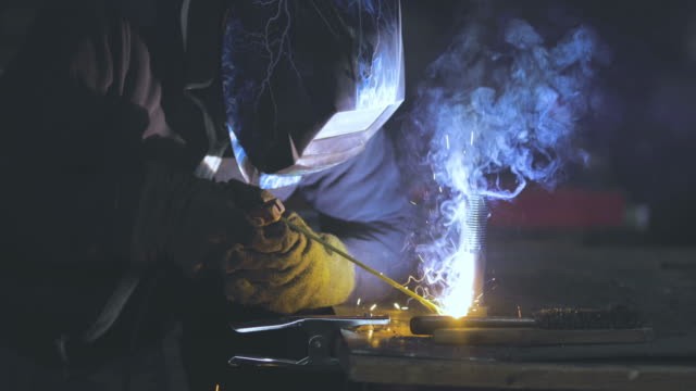 Unrecognizable steel worker welding metal in a factory.